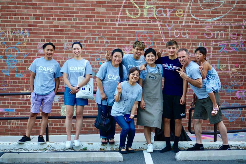 A group of CAFE volunteers standing in front of a chalk art wall.